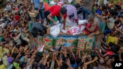Rohingya Muslims, who crossed over from Myanmar into Bangladesh, stretch their arms out to collect food items distributed by aid agencies near Balukhali refugee camp, Bangladesh, Sept. 18, 2017.