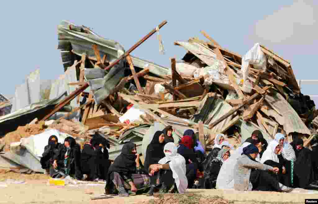 Arab Israeli women sit next to the ruins of their dwellings which were demolished by Israeli bulldozers in Umm Al-Hiran, a Bedouin village in Israel's southern Negev Desert.