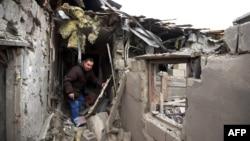 ຊາຍຄົນນຶ່ງຍ່າງ ຢູ່ໃນເຮືອນຫຼັງນຶ່ງ ທີ່ຖືກທຳລາຍ ໃນຄຸ້ມ Leninsky ເມືອງ Donetsk, ພາກຕາເວັນອອກຂອງຢູເຄຣນ, ວັນທີ 8 ກຸມພາ 2015.