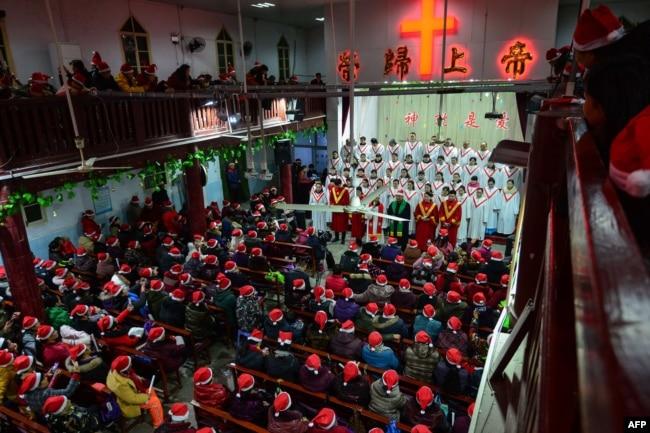 """2018年12月24日,人们在中国安徽省阜阳市的一个教堂参加圣诞节前夜活动。墙上有口号""""荣归上帝""""""""神就是爱""""。"""