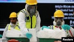 FILE - Police officers destroy seized cocaine under judicial supervision in Katunayake, Sri Lanka, Jan. 15, 2018.