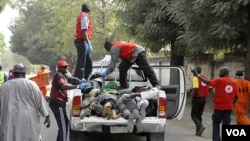 Petugas mengangkut jenazah para korban tewas dalam ledakan bom di kota Kano, Nigeria utara (21/1).