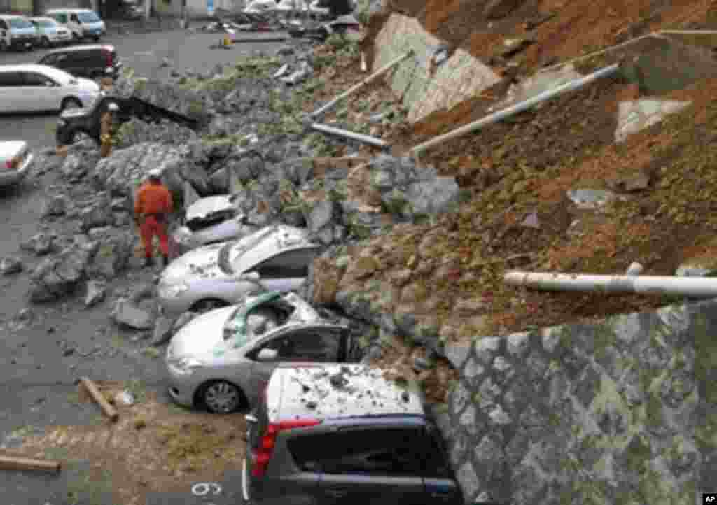 Vehicles are crushed by a collapsed wall at a carpark in Mito city in Ibaraki prefecture after a massive earthquake rocked Japan, March 11, 2011 - (AFP)