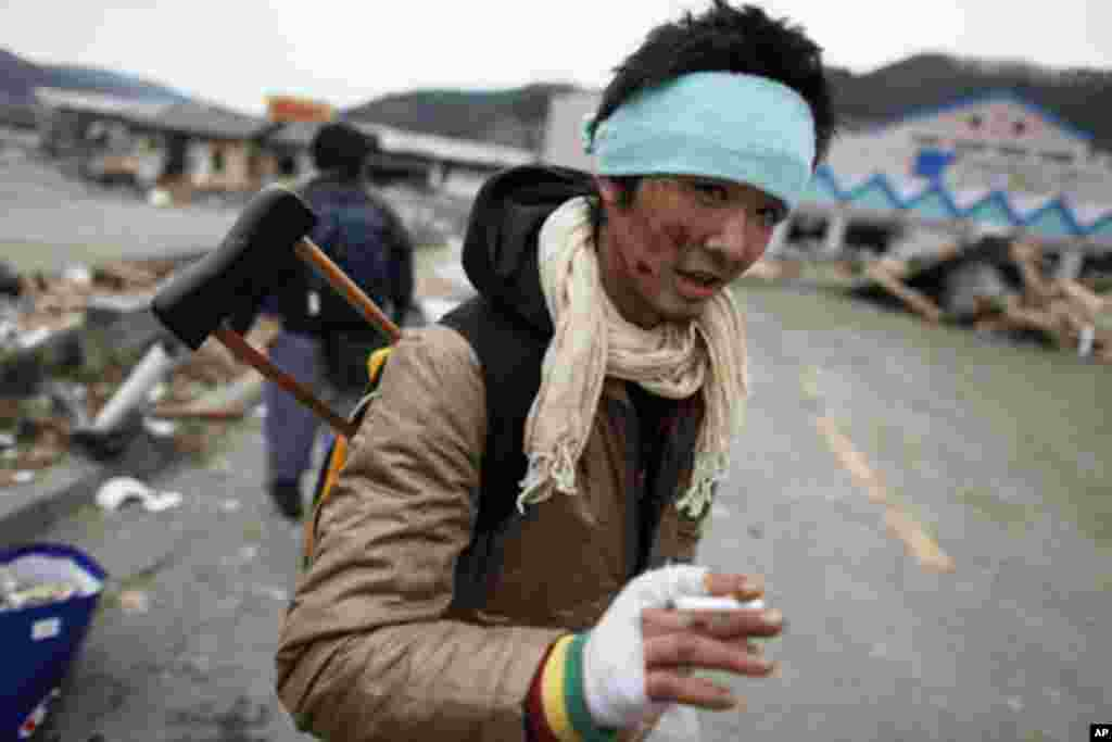 An injured survivor searches for food at a destroyed supermarket in the devastated residential area of Otsuchi March 15, 2011. In the fishermen town of Otsuchi in Iwate prefecture, 12,000 out of a population of 15,000 have disappeared following last Frida
