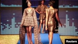 Models wear creations by designer and organizer of Dakar Fashion Week Adama Paris (Ndiaye) during the 10th annual event in the Senegalese capital of Dakar, Senegal, June 17, 2012.