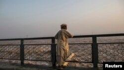ایک پاکستانی کسان دریائے سندھ کا بہاؤ دیکھ رہا ہے۔