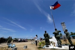 A FFILE - Filipinos conduct a flag raising ceremony at Pag-asa Island in the Spratly Islands