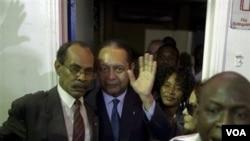 Diktatè ayisyen Jean-Claude Duvalier (nan mitan foto a) k ap salye jounalis yo apre nan moman li pral ranpli fòmalite imigrasyon nan ayewopò entènasyonal Toussaint Louverture nan Pòtoprens, Ayiti. Dimanch 16 janvye 2011