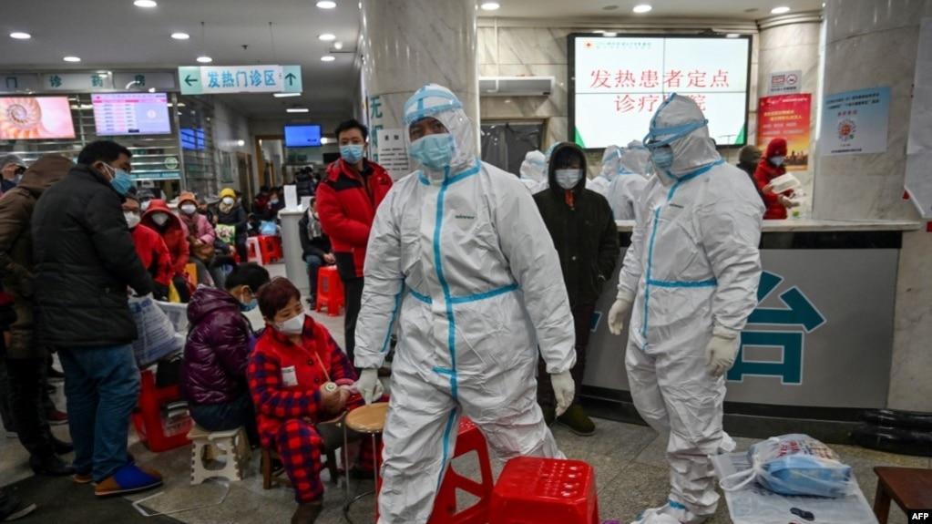 资料照:武汉红十字医院身穿防护服的医务人员和等候就诊的病患。(2020年1月25日)