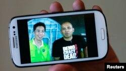 Peter Chong sostiene un teléfono en el que aparece junto al capitán Zaharie Ahmad Shah (derecha).