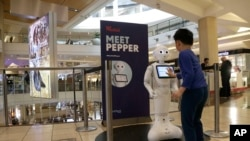 A boy gets to know Pepper the robot at the Westfield Mall in San Francisco, Dec. 22, 2016. Pepper has trouble understanding what people are asking, requiring shoppers to type in their requests for mall directions on a tablet mounted on the robot's chest.