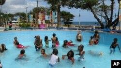 Anak-anak bermain di kolam renang di Santo Domingo, Republik Dominika. (AP/Ezequiel Abiu Lopez)