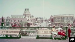 FILE - Visitors look down the Main Street section of Disneyland from the railroad station platform in Anaheim, California, June 7, 1955. Oscar Martinez, 81, is set to celebrate 60 years as a Disneyland employee. He began working there a year after the park's opening.