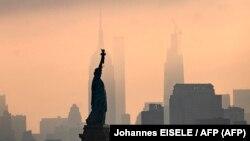 La Statue de la Liberté est vue devant l'Empire State Building au lever du soleil le 9 juillet 2020 à New York.