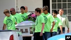Pallbearers wearing anti-bullying t-shirts carry the casket of 12-year-old Rebecca Sedwick. Authorities believe she killed herself after being bullied. (2013)