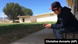 In this April 30, 2015 photo, Brian Olivas, 17, looks at his smartphone between classes at the Cuyama Valley High School in New Cuyama, California. The Cuyama Joint Unified School District is 60 miles from the nearest city.