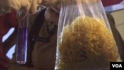 Petugas BBPOM Bandung menunjukkan sampel mie yang diperoleh dari pasar Tradisional Ancol di Bandung. Setelah diuji, cairan kimia dalam tabung berubah warna menjadi ungu (Foto: VOA/Teja Wulan)