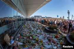Flight attendants and mourners gather near flower bouquets as they pay their respects at Schiphol Airport during a national day of mourning for the victims of the downed Malaysia Airlines flight MH17, in Schiphol July 23, 2014.