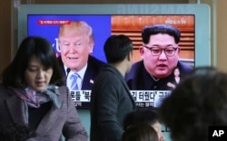 A man watches a TV screen showing file footage of U.S. President Donald Trump, left, and North Korean leader Kim Jong Un during a news program at the Seoul Railway Station in Seoul, South Korea, Monday, April 9, 2018.
