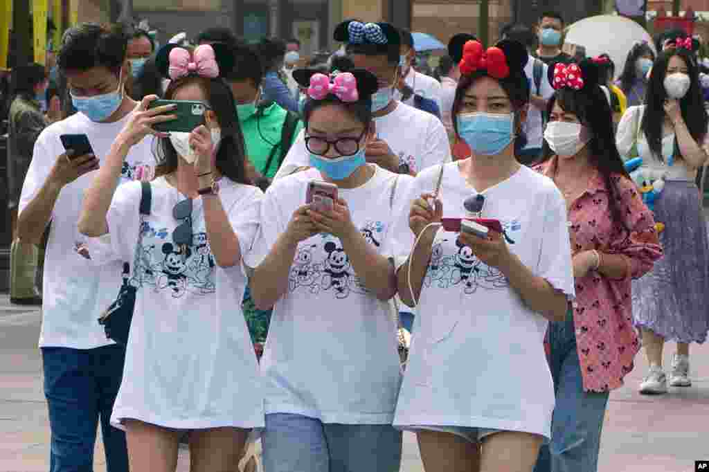 Visitors, wearing face masks, enter the Disneyland theme park in Shanghai, China.