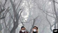 Chinese women wearing masks for protection against air pollution walk through Ritan Park shrouded by dense smog in Beijing, Dec. 19, 2016.