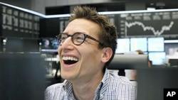 图为德国股指8月11日反弹,一名交易者喜笑颜开