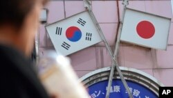 A woman walks past an advertisement with Japanese and South Korean flags at a shop in Shin Okubo area in Tokyo Friday, Aug. 2, 2019.