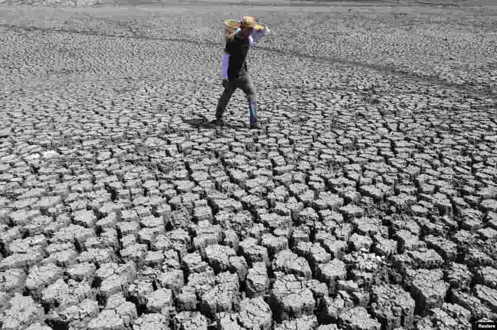 A man walks on cracked ground at the Las Canoas dam, some 59 km (37 miles) north of the capital Managua, Nicaragua, Apr. 26, 2013.