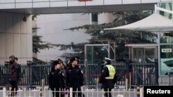 FILE - Policemen stand guard in front of the court building in Beijing.
