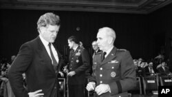 FILE - In this Feb. 1, 1983 file photo, Sen. Edward Kennedy, D-Mass, left, a member of the Senate Armed Services committee, talks with the chairman of the Joint Chiefs of Staff, Gen. John W. Vessey, on Capitol Hill.