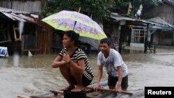 Warga membuat rakit darurat untuk melewati banjir yang disebabkan oleh badai tropis Agaton, di Butuan, bagian selatan pulau Mindanau 19 Januari 2014.