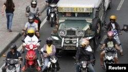 Pengendara sepeda motor dan angkutan jeepney saat menunggu lampu hijau di jalan di Paranaque, Metro Manila, 2 Maret 2016.