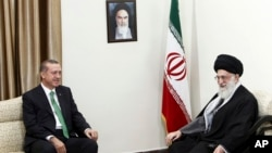 Supreme Leader Ayatollah Ali Khamenei (R) and Turkish Prime Minister Recep Tayyip Erdogan talk during their meeting in Tehran, Iran, Jan. 29, 2014. A portrait of the late Iranian revolutionary founder Ayatollah Khomeini hangs on the wall.