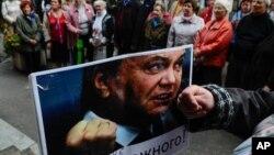 """Eine Teilnehmerin einer Demonstration gegen Wahlbetrug haelt am Mittwoch (26.09.12) in Kiew, Ukraine, ein Bild des ukrainischen Praesidenten Wiktor Janukowitsch mit der Unterschrift """"Ich werde mir jedermanns Forderungen anhoeren!"""""""