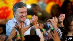 Outgoing Buenos Aires Mayor Mauricio Macri holds hands with followers after a mayoral runoff election — won by conservative candidate Horacio Rodriguez Larreta — in Buenos Aires, July 19, 2015.