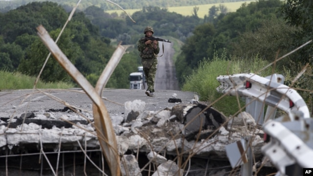 An Ukrainian government army  soldier approaches to a damaged  bridge near the village of Debaltseve, Donetsk region, eastern Ukraine, July 31, 2014.