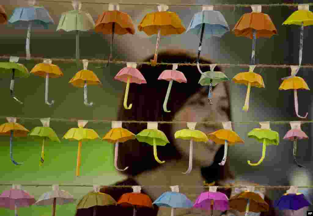 A woman poses for a photo with the paper fold umbrellas at the occupied area in Causeway Bay, a shopping district of Hong Kong.
