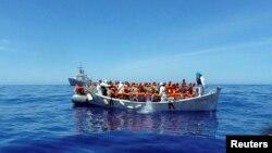 Para migran duduk di perahu mereka dalam operasi penyelamatan oleh kapal angkatan laut Italia di lepas pantai Sisilia (6/5).