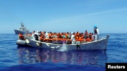 Migrants sit in their boat during a rescue operation by the Italian navy off the coast of Sicily in this handout picture from the Italian Marina Militare, released May 6, 2016. Italy's coast guard rescued about 1,000 people off the country's southern tip Thursday.