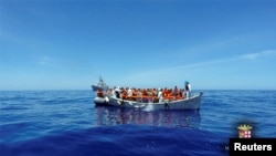 FILE Migrants sit in their boat during a rescue operation by Italian navy ship Grecale (unseen) off the coast of Sicily in this handout picture from the Italian Marina Militare, released May 6, 2016.