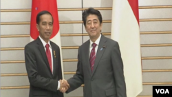在日本訪問的印尼總統佐科·維多多(左)與日本首相安倍晉三握手。(視頻截圖)