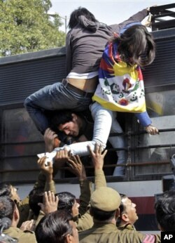 Tibetan exiles try to escape from a police vehicle after being detained during a protest outside the Chinese Embassy in New Delhi, India, Thursday, Feb. 16, 2012. Tibetan exiles try to escape from a police vehicle after being detained during a protest out