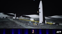 Billionaire entrepreneur and founder of SpaceX Elon Musk speaks below a computer-generated illustration of his new rocket at the 68th International Astronautical Congress 2017 in Adelaide, Australia, Sept. 29, 2017.