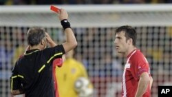 Argentine referee Hector Baldassi, left, gives a red card to Serbia's Aleksandar Lukovic during the World Cup group D soccer match between Serbia and Ghana at the Loftus Versfeld Stadium in Pretoria, South Africa, Sunday, June 13, 2010.