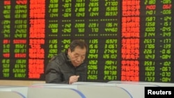 An investor looks at a computer screen showing stock information at a brokerage house in Fuyang, Anhui province, Jan. 28, 2016.