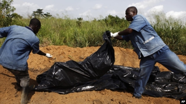 Red Cross workers dump unidentified bodies into a mass grave in Ivory Coast's main city Abidjan (2011 file).