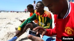 FILE - A Somali man browses the internet on his mobile phone at a beach in Somalia's capital Mogadishu, January 10, 2014.