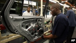 In this Feb 1, 2008 file photo Hyundai Motor Company employees work on vehicles at the Montgomery, Ala. plant.