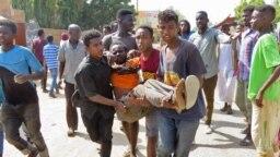 Beberapa pengunjuk rasa tampak mengangkut seorang pria yang terluka saat bentrokan terjadi dalam aksi unjuk rasa menentang kudeta militer di Khartoum, Sudan, pada 25 Oktober 2021. (Foto: AFP)