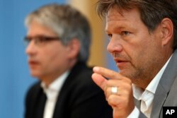 Sven Giegold, background, top candidate of the European Green Party, and Robert Habeck, chairman of the Green Party, attend a news conference after the elections for the European Parliament in Berlin, Germany, May 27, 2019.